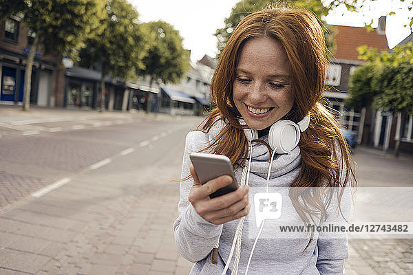 Redheaded woman using headphones and smartphone in the city
