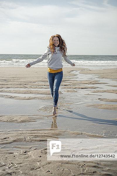 Happy woman having fun at the beach  running at the sea