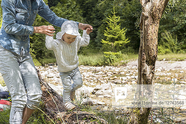 Mother holding hands of daughter  balancing on tree trunk