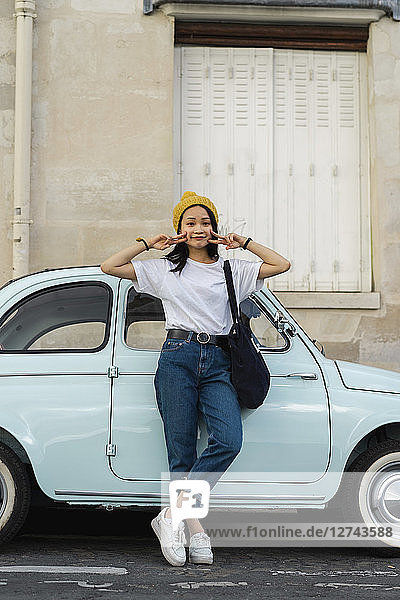 Portrait of young woman standing at small car