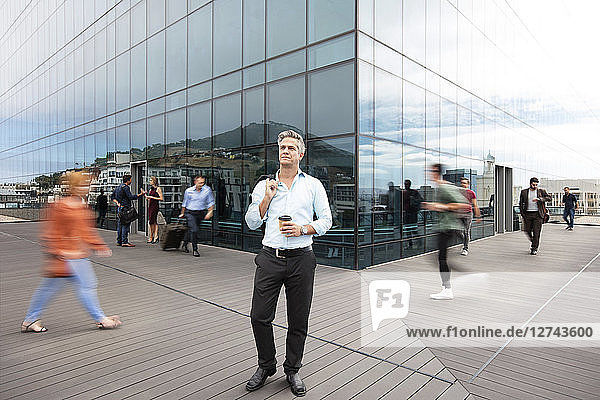 Businessman holding cup of coffee  people walking around him