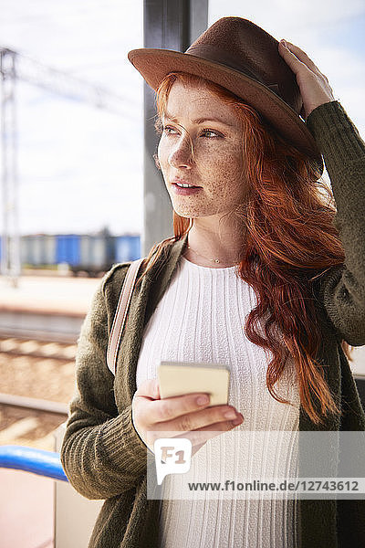 Portrait of redheaded woman with hat and smartphone at platform