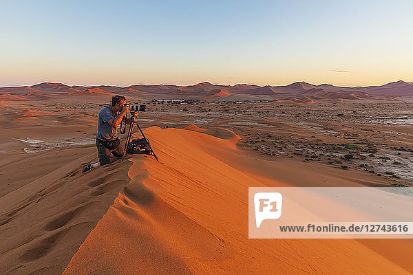 Africa  Namibia  Namib desert  Naukluft National Park  photograper on sand dune at sunrise