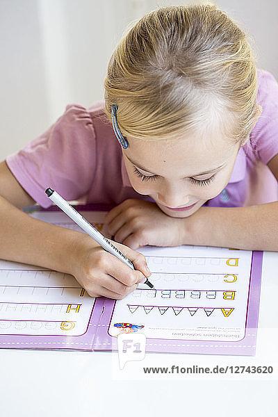 Little girl writing alphabet