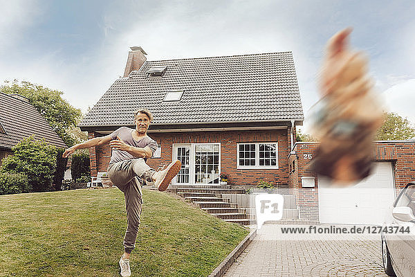 Mature man kicking away garden gnome in front of his home