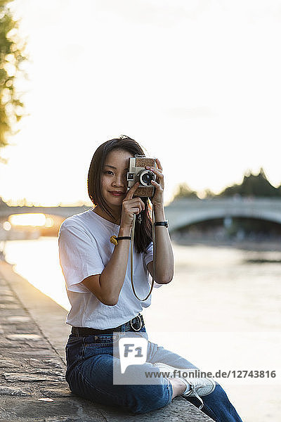 France,  Paris,  portrait of young woman with camera at river Seine at sunset