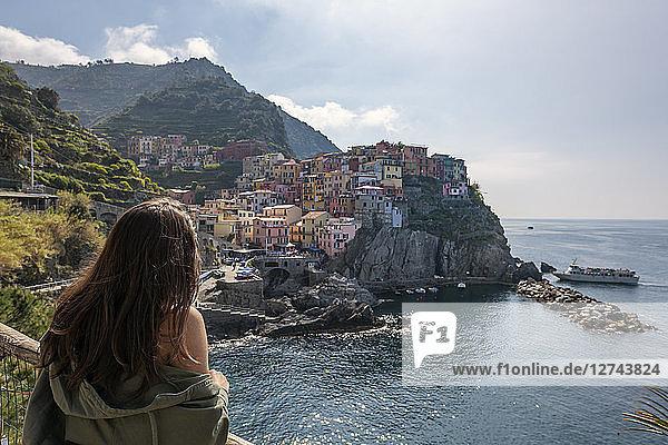 Italy  Liguria  La Spezia  Cinque Terre National Park  young woman looking to Manarola