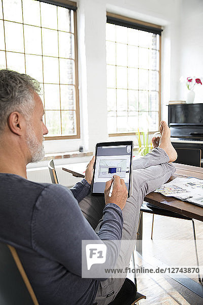Mature man working from his home office with feet up  using laptop