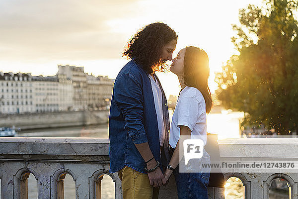 France,  Paris,  affectionate young couple at river Seine at sunset