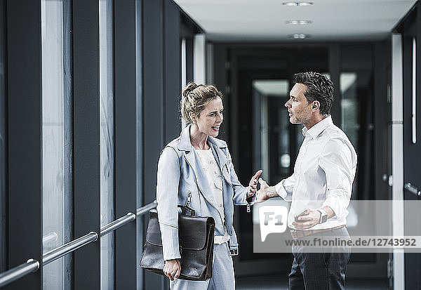 Businesswoman and businessman arguing in office passageway