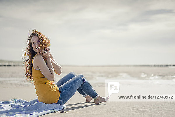 Woman sitting on the beach  laughing