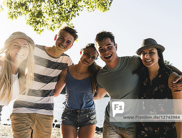 Portrait of group of happy friends arm in arm at the riverside