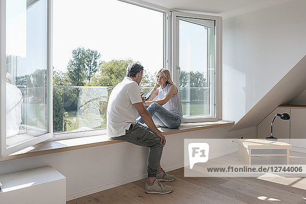 Mature couple with cell phone sitting at the window in empty room