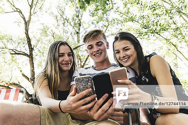 Three happy friends looking at cell phones outdoors