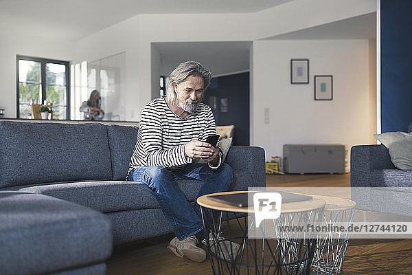Senior man sitting on couch  using smartphone