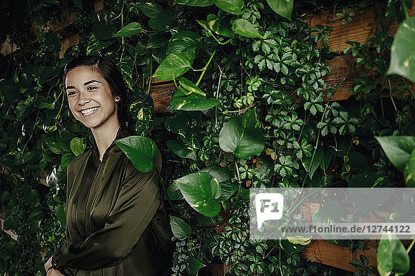 Happy young woman at wall with climbing plants