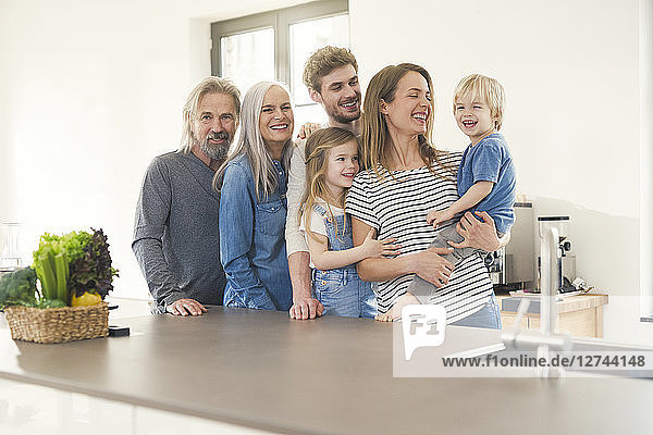 Happy family with grandparents and children standing in the kitchen