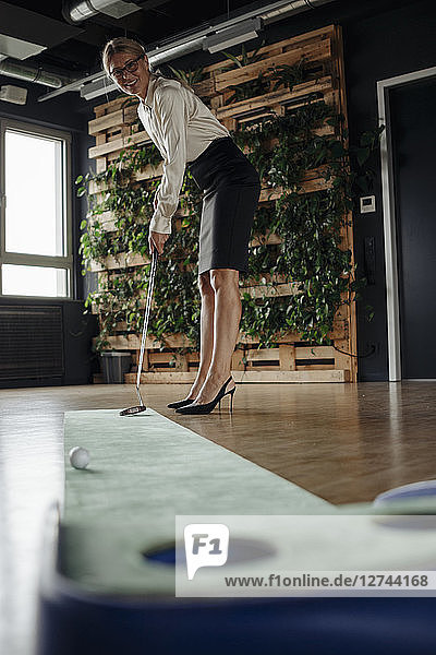 Businesswoman playing golf in office