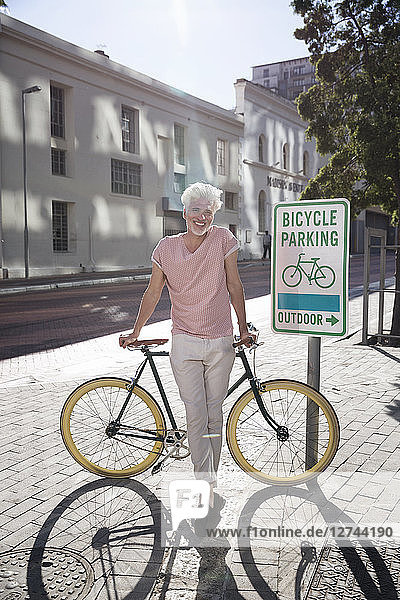 Mature man in the city leaning on his bicycle