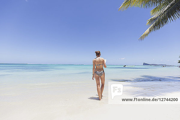 Mauritius  Cap Malheureux  young woman standing in water  reading a book  rear view