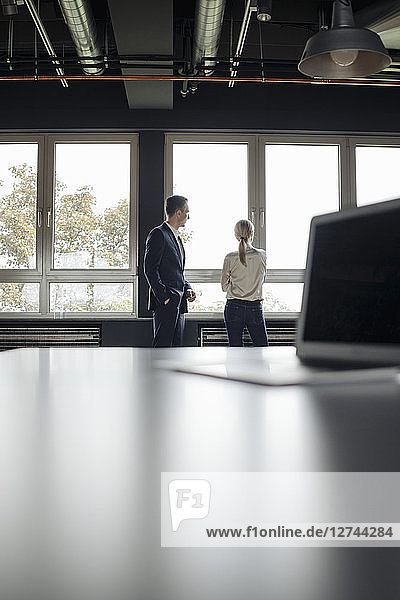 Businessman and businesswoman standing at the window and laptop on table