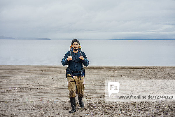 Man with backpack  walking on the beach