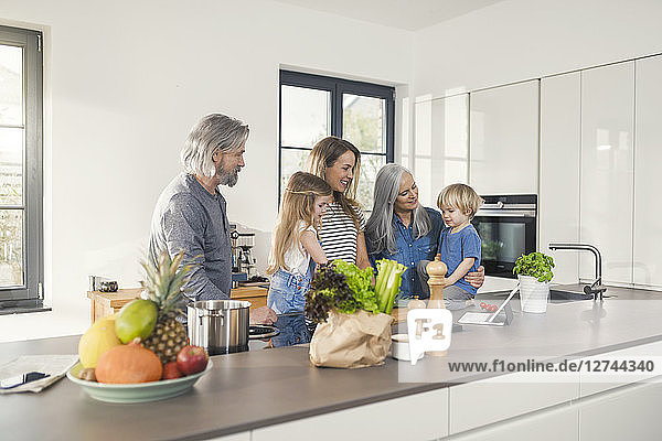 Grandparents with grandchildren and their mother standing in kitchen