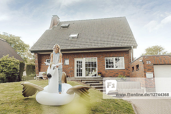 Portrait of smiling mature woman with inflatable pool toy in garden of her home