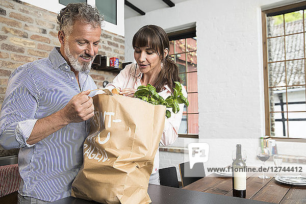 Mature man bringing grocery bag full of purchase to the kitchen