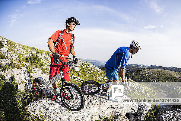Acrobatic bikers with trial bikes on rock