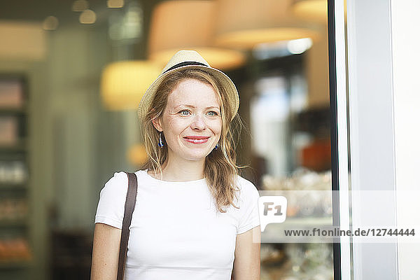 Young woman with hat leaving shop