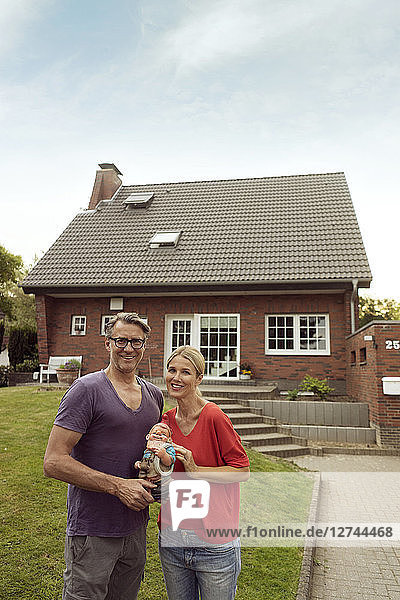 Portrait of smiling mature couple standing in front of their home holding garden gnome