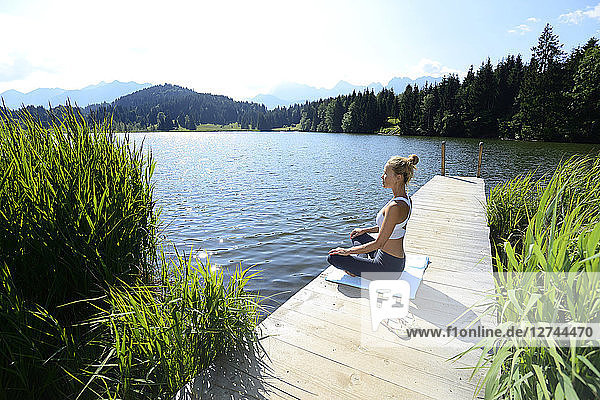Germany  Mittenwald  woman practising yoga on jetty at lake