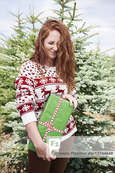 Redheaded young woman with Christmas present outdoors