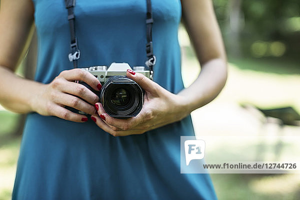 Woman's hands holding analogue camera  close-up