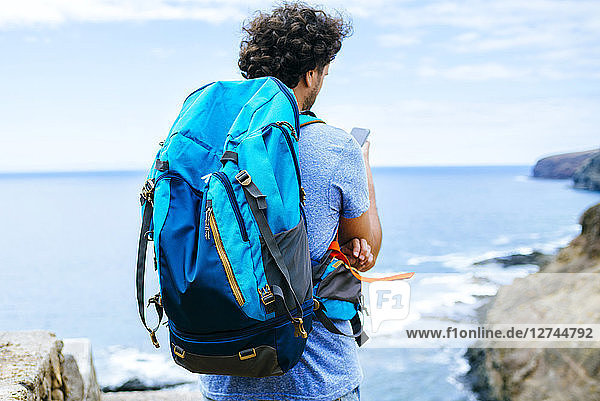 Spain  Canary Islands  Gran Canaria  Close-up of man with backpack using mobile phone