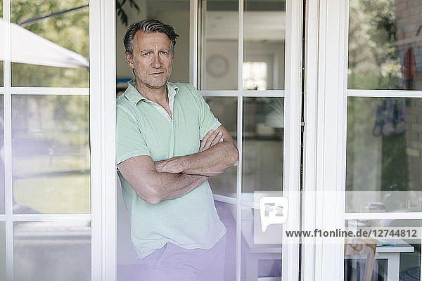 Portrait of serious mature man standing at French window
