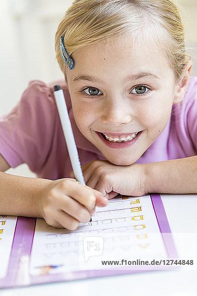 Portrait of smiling little girl writing alphabet