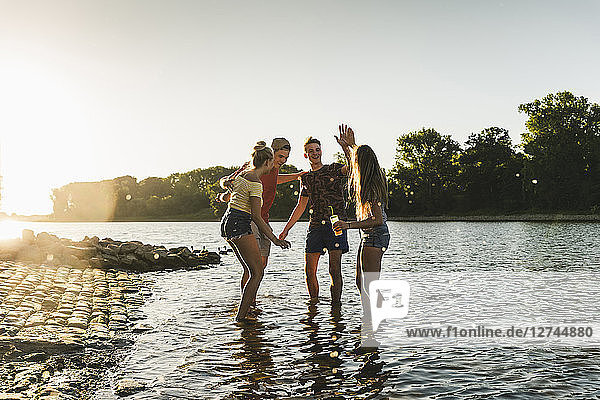 Group of happy friends in a river at sunset