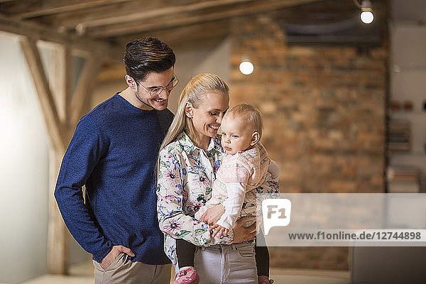 Happy young parents spending time at home with their baby girl