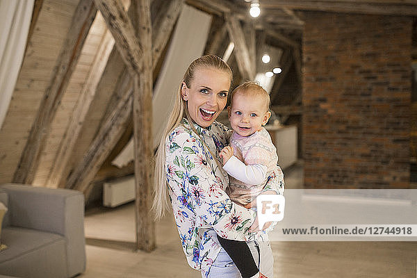 Portrait of happy mother with her baby girl at home