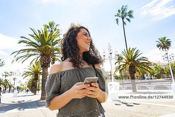 Smiling teenage girl holding smartphone at waterfront promenade