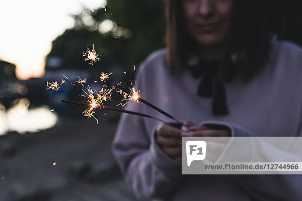 Young woman holding sparklers in the evening