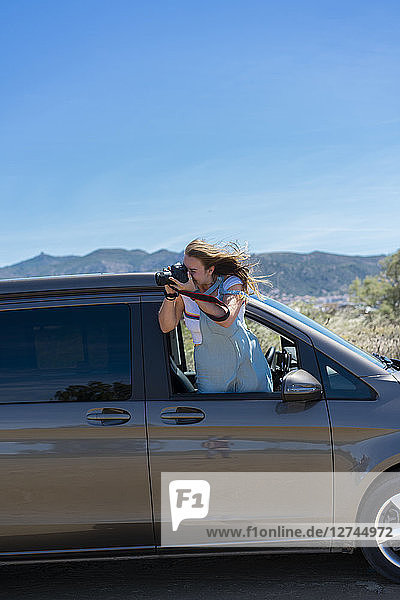 Happy woman leaning out of car window  taking pictures