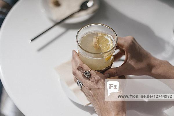 Woman holding glass of ginger lemon tea