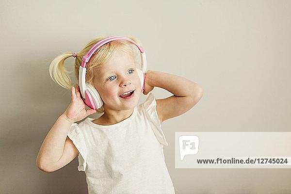 Portrait of little girl listening music with headphones dancing