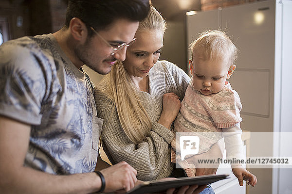 Young parents using tablet at home with their baby girl
