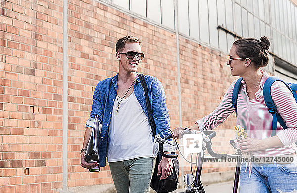 Young couple with bicycle walking and talking