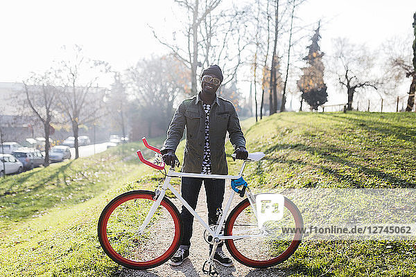 Young holding bicycle in park