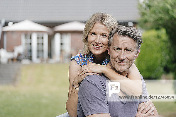 Portrait of smiling mature couple embracing in garden of their home